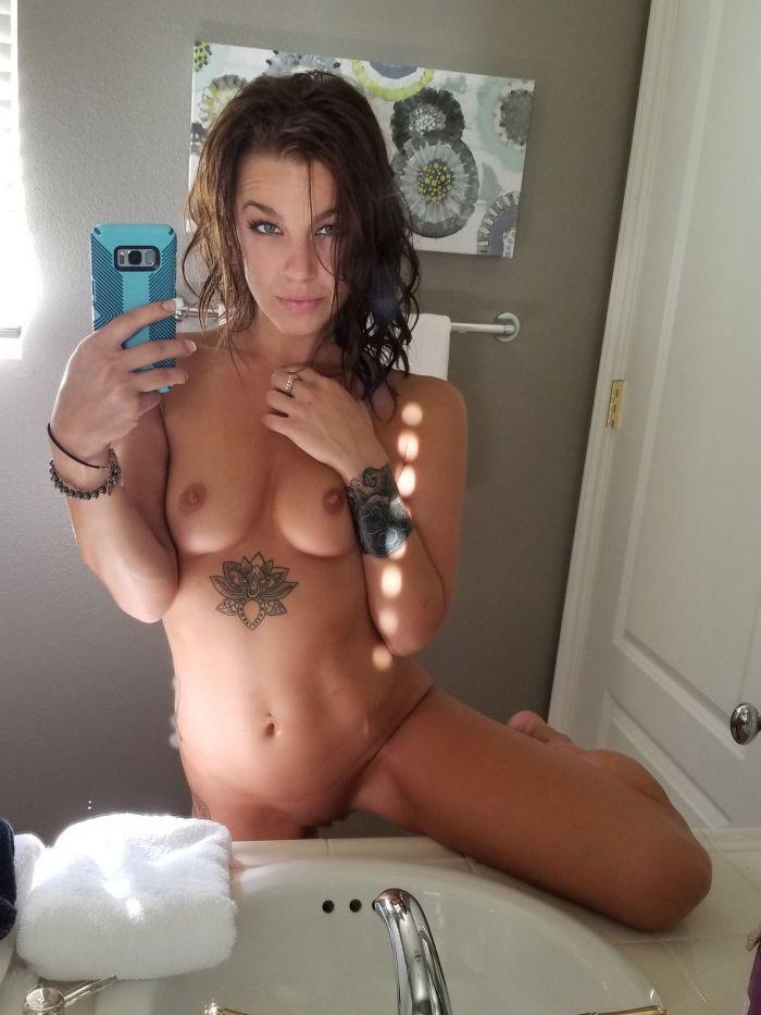 Selfie d'une magnifique brune tatouée entièrement nue
